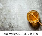 glass jar with honey . on a... | Shutterstock . vector #387215125