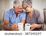 senior couple sitting on sofa... | Shutterstock . vector #387245197