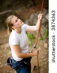 A female belaying a male on a steep rock face.  Shallow depth of field has been used to isolated the belayer, with focus on the eyes and head. - stock photo
