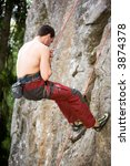 A male climber repells down a rock face - crag. - stock photo