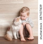 boy hugging cat at home while... | Shutterstock . vector #387437839
