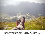 Small photo of Legs of traveler sitting on a high mountain top in travel. Freedom concept