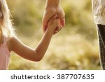 a the parent holds the hand of... | Shutterstock . vector #387707635