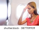 Small photo of Fear of flying woman in plane airsick with stress headache and motion sickness or airsickness. Person in airplane with aerophobia scared of flying being afraid while sitting in airplane seat.