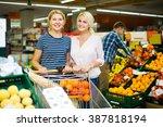 two woman choosing seasonal... | Shutterstock . vector #387818194