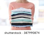 Stock photo woman hold clothes pile close up 387990874