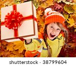 Girl in autumn orange  hat on leaf and gift box.Outdoor. - stock photo