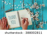 Small photo of woman hand writing a note with the text thank you on a notebook, over wooden table and cherry blossom flowers