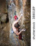 A male climber viewed from above climbs a steep crag. Shallow depth of field is used to isolate the climber with focus on the hands and head - stock photo