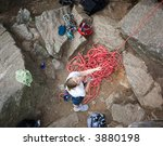 A female climber belaying - viewed from above.  A shallow depth of field is used to isolate the climber - with focus on the eyes and head. - stock photo