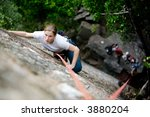A female climber on a steep rock face.  Shallow depth of field is used to isolated the climber.  Focus is on the head, shoulders and arms of the climber. - stock photo