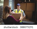 Delivery Driver Handing Parcel...