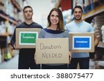 Small photo of Volunteers smiling at camera holding donations boxes in a large warehouse