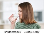 young woman drinking water from ... | Shutterstock . vector #388587289