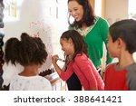 pupil writing on the board at... | Shutterstock . vector #388641421