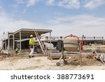Cement mixer machine at construction site, tools, sand and cement bag. - stock photo