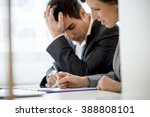 Small photo of Business colleagues, man and woman, working at office desk reading a report or document looking a bit stressed and agitated. Focus to her hand.
