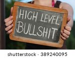 Small photo of HIGH LEVEL BULLSHIT written with chalk on writing slate shown by young female