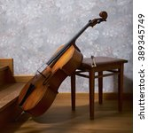 Small photo of Old cello, bow and stool next to gently sun alight stairs.