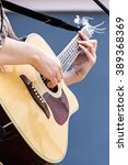 Small photo of closeup of woman hands playing acoustic guitar outdoors
