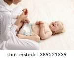 mother changing baby diaper | Shutterstock . vector #389521339