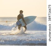 Male Surfer On The Beach With...
