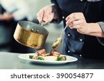 chef pouring sauce on dish in... | Shutterstock . vector #390054877