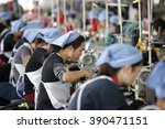 female labors work in a cloth... | Shutterstock . vector #390471151