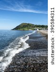 Ireland, County Wicklow, Bray: Shoreline of Irish spa seaside resort Bray with waves, Bray Head and blue sky in the background.