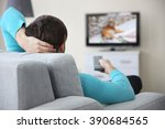 young handsome man watching tv... | Shutterstock . vector #390684565