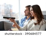 young couple watching tv on a... | Shutterstock . vector #390684577