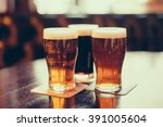 glasses of light and dark beer... | Shutterstock . vector #391005604