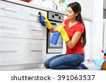 Stock photo beautiful woman in protective gloves cleaning kitchen cabinet 391063537