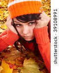 Girl in orange hat on leaves with sad face.  Autumn depression. - stock photo
