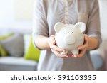 female hands holding piggy bank ... | Shutterstock . vector #391103335
