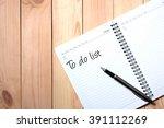 note book with black pen.... | Shutterstock . vector #391112269