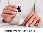 girl paints her nails white... | Shutterstock . vector #391123111