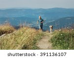 Stock photo man runs with his dog on the green meadow in mountain 391136107
