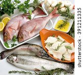Small photo of Fish composition with vegetables, garlic, rosemary and parsley with oil, trout, snapper and cod
