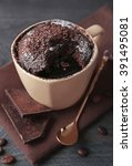 Small photo of Chocolate fondant cake in cup on wooden table closeup