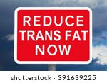 Small photo of Red and white signpost REDUCE TRANS FAT NOW in front of a dark sky, symbol for the health risk of high trans-fat consumption by eating a lot of fast-food, spoof of british road signs