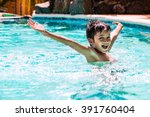 Young boy kid child eight years old splashing in swimming pool having fun leisure activity open arms - stock photo