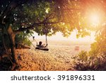 Small photo of Happy boy kid on swing enjoy freedom and summer on sea shore on sunset
