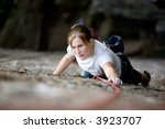 A female climber on a steep rock face looking for the next hold.  Shallow depth of field is used to isolate the climber. - stock photo