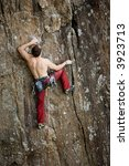 A male climber against a large rock face climbing lead against a magnificant landscape. - stock photo