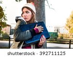 Small photo of scared woman trying to protect her laptop pc and data looking helpless and vulnerable - privacy and identity theft concept - custom color tones and contrast effects added to add drama