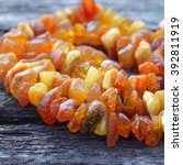 Small photo of Bright orange amber necklace of raw beads/Necklace of amber beads/Amber beads string on an old gray wooden background, closeup