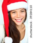 Christmas girl in a Santa hat smiling. Very beautiful mixed asian / caucasian model. Isolated on white background. - stock photo