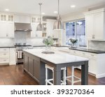 Stock photo beautiful kitchen in luxury home with island pendant lights cabinets and hardwood floors tile 393270364
