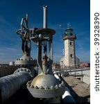 A stone lighthouse next to a fuel valve system. - stock photo